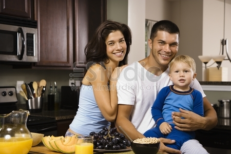 Caucasian family with toddler son in kitchen at breakfast smiling at viewer.