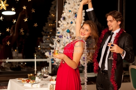 Happy young couple with champagne glasses in hand dancing at Christmas