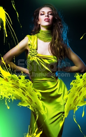 Sensual beautiful woman in green dress and paint splash