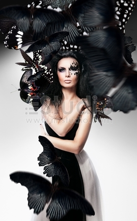 Woman with black hair and art make up and black butterflies