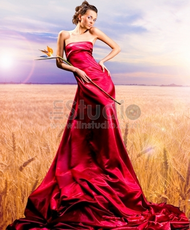 Beautiful girl in red dress. Golden wheat ready for harvest growing in a farm field