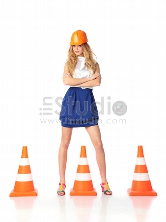 Sexy female construction worker with orange traffic cones