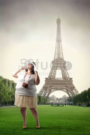 Fat woman standing in front of the Eiffel Tower