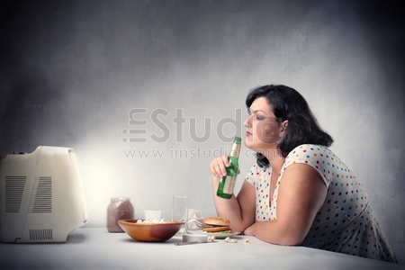 Fat woman sitting in front of the television and drinking a beer