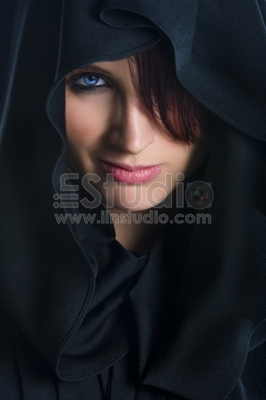 Image of mysterious woman wearing black cloak