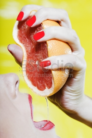 beautiful woman portrait with colorful make-up and background drinking grapefruit juice