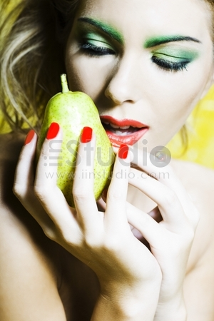 beautiful woman portrait with colorful make-up and background holding pear