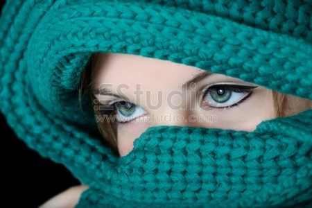 Young woman with black kohl make-up on eyes in traditional Middle East fashion covering her face with green scarf