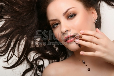 attractive young woman lying on white background with chocolate smeared