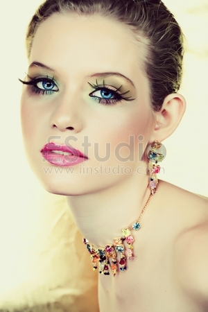 Beautiful blond woman with long lashes and colourful stones necklace and earrings and seductive smile ? not isolated