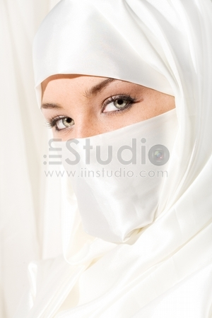 Close up face shot of woman in white face veil