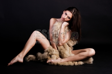 Portrait of beautiful young woman with fur coat