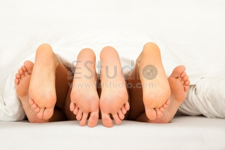 Three pairs of feet having fun in the bed having a threesome