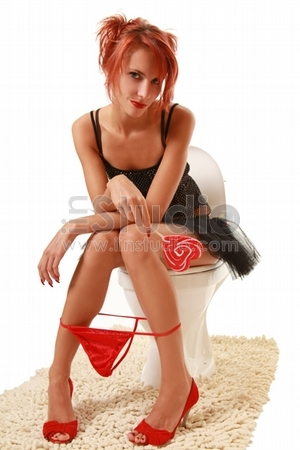 funny girl with red lollipop in the toilet