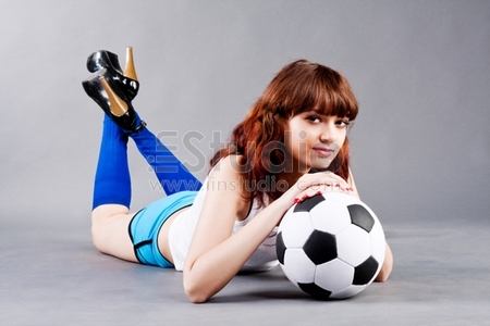 girl on floor with a soccer ball