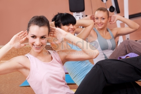Joyful young women working out in fitness club