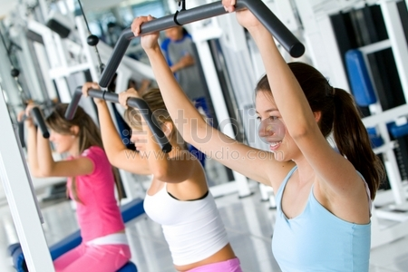 beautiful women at the gym doing exercises on a machine