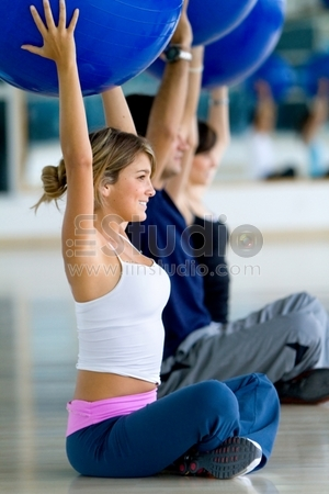 group of people at the gym smiling with pilates balls