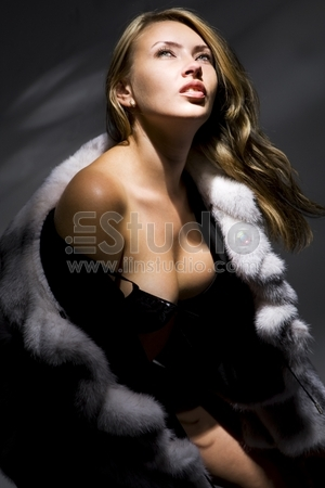 Attractive woman in fur coat looking up