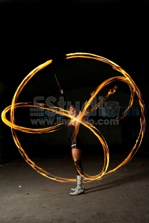 Flaming poi concept. Attractive and sexy girl spinning flaming poi in front of camera