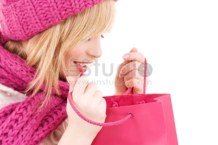 Happy teenage girl in hat with pink shopping bags
