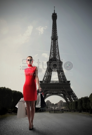 Woman in red dress carrying some shopping bags with the Eiffel tower on the background