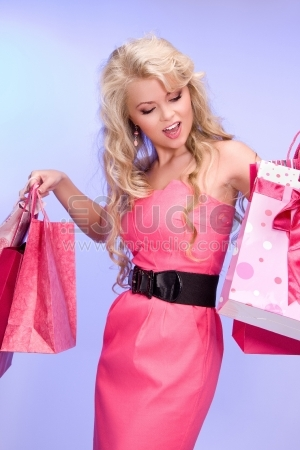 Lovely woman with shopping bags over blue