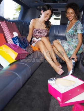 Women in limousine trying on new shoes