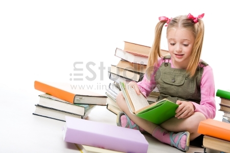 Portrait of pretty schoolgirl reading textbook near pile of books