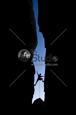 Rock climber silhouetted as he climbs up a chimney in Joshua Tree National Park, California, on a summer day