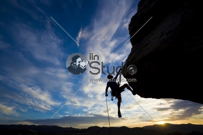 Rock climber rappelling past an overhang in Joshua Tree National Park