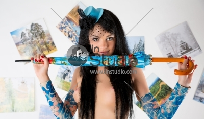 pretty girl in nude on studio with colorful umbrella