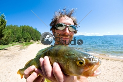 Caucasian man caught perch, at lake shore