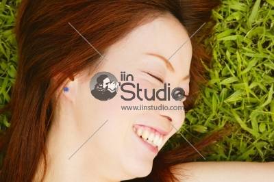Beautiful Young Woman lying in Grass - Enjoy Nature
