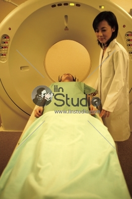 Radiologic technician smiling at mature female patient lying on a CT Scan bed