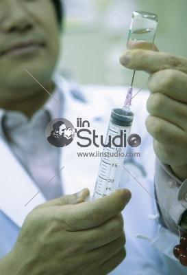 Doctor filling a syringe